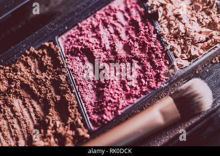 crushed blush and bronzer powders with brush close-up shot, concept of beauty and make-up products - Stock Image