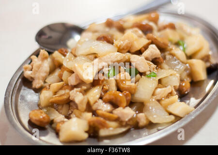 cashew chicken onions Chinese food on metal dish - Stock Image