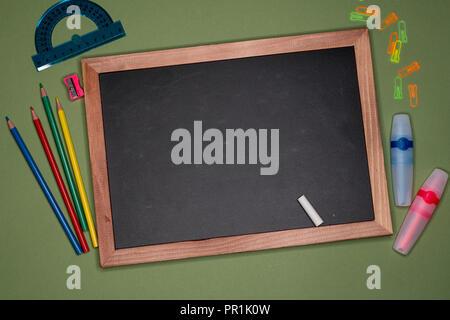 School concept. Empty blackboard, stationery on green background, blank copy space. - Stock Image