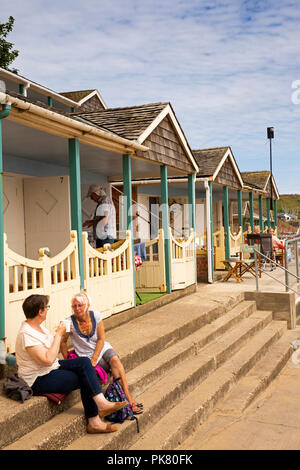 UK, England, Yorkshire, Filey, visitors drinking tea at Coble Landing beach hut steps - Stock Image