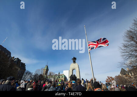OTTAWA, CANADA - NOVEMBER 11, 2018: Union Jack flag in front of a Crowd gathering on National War memorial, on remembrance day to commemorate the cana - Stock Image