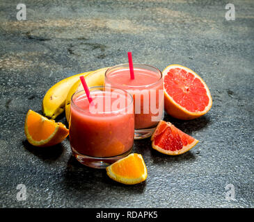 Fruit smoothie in glasses. On rustic background. - Stock Image
