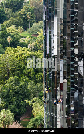Workers cleaning windows on a high rise residential building in Brisbane. - Stock Image