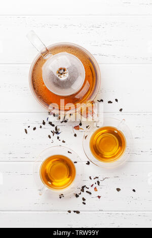 Herbal and fruit teas, teapot and cups on wooden table. Top view flat lay - Stock Image