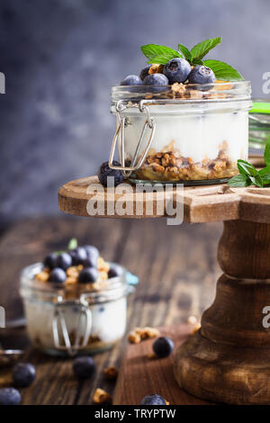 Healthy breakfast of blueberry parfaits made with fresh fruit, Greek yogurt, granola and mint leaves over a rustic cake stand.  Selective focus on gla - Stock Image