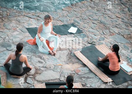 Ocean front meditation, multiple women. Yoga retreat Puerto Vallarta - Mismaloya, Mexico - Stock Image