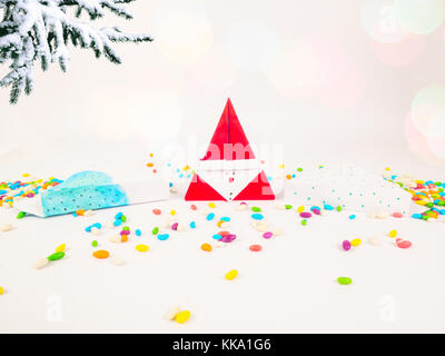 Christmas decoration triangle git boxes with colorful candy as confetti under christmas tree for celebration best - Stock Image