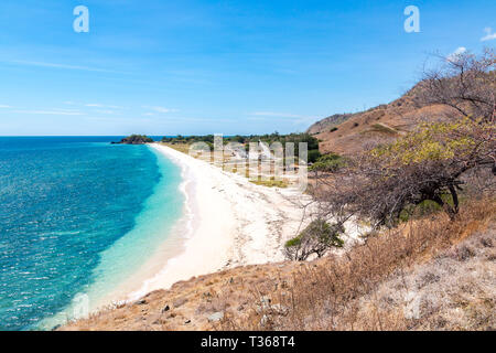 One dollar beach. Idillic yellow sandy beach of East Timor, Timor-Leste. Coastline with hills, mountains and dry savanna. Rural landscape and nature b - Stock Image