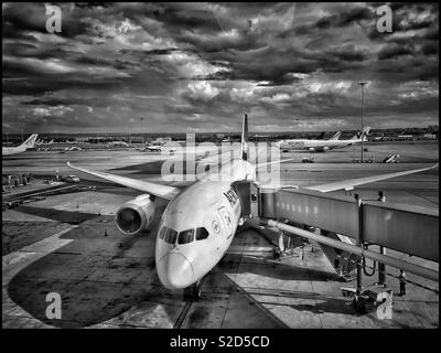 An atmospheric aerial view of aircraft at a large European airport. Despite the sunshine, it looks like rain is on the way! Photo Credit © COLIN HOSKINS. - Stock Image