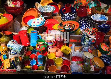 Display of colourful pottery cups jugs and dishes on a French market stall - Stock Image