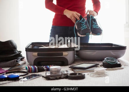 Woman packing suitcase, holding trainers, mid section - Stock Image