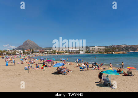 Javea Spain Playa del Arenal beach in summer with blue sky sea and people, also known as Xabia - Stock Image