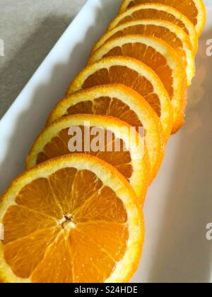 Orange slices on a white plate - Stock Image