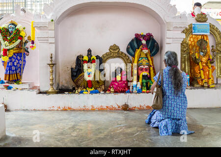 Woman Praying to Hindu Deities, Hindu Sri Maha Muneswarar Temple, Kuala Lumpur, Malaysia. - Stock Image