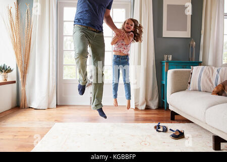 Girl and dad jumping in the air at home holding hands - Stock Image