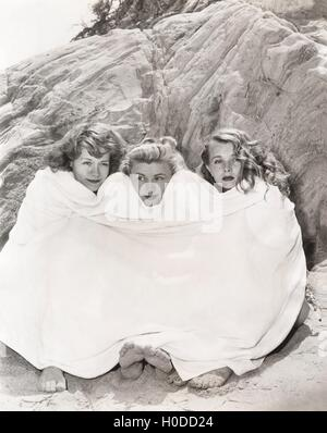 Three women huddled under a towel on beach - Stock Image