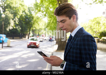Young businessman standing in the street using smartphone - Stock Image