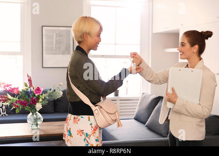 Real estate agent giving apartment keys to young woman - Stock Image