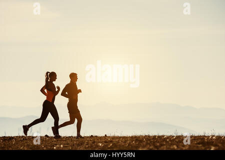 Couple of runners in steppe on mountains backdrop - Stock Image