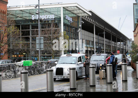 View passengers with luggage paying taxi driver at St Pancras Station building Pancras Road at Kings Cross & tourist Big Bus London UK  KATHY DEWITT - Stock Image