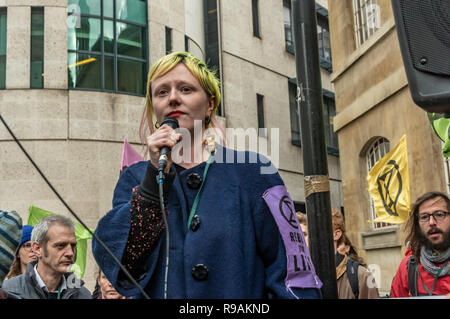 London, UK. 21st December 2018. Claire from Extinction Rebellion speaks at the protest at the BBC calling it to stop ignoring the climate emergency & mass extinctions taking place and promoting destructive high-carbon living through programmes such as Top Gear and those on fashion, travel, makeovers etc. The protest, organised by the Climate Media Coalition (CMC) and its director Donnachadh McCarthy brought mannequins wrapped in white cloth to the BBC representing the bodies of a Greek village killed by fire. Peter Marshall/Alamy Live News - Stock Image
