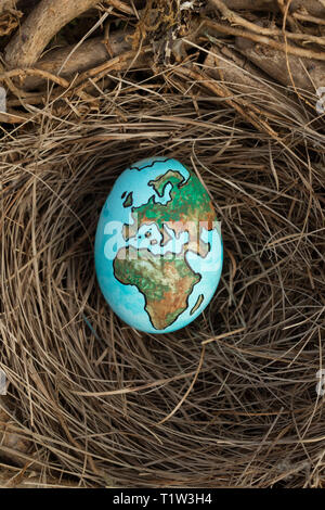 Planet Earth painted on an egg in a birds nest. - Stock Image