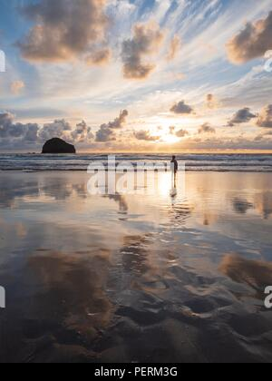 A boy stood alone on a beach at sunset with the reflection of the sky in the wet sand - Stock Image