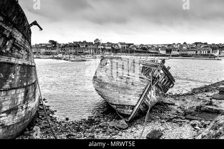 Ragged and crumbling timber fishing boats at the ship graveyard in Camaret-sur-Mer in Brittany, France. - Stock Image