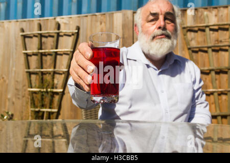 Middle-aged man with raised blackcurrant fruit squash drink in a glass, leaning forward at a glass table in a UK - Stock Image