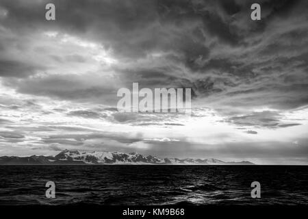 Brooding storm clouds gather off the shore of Svalbard - Stock Image