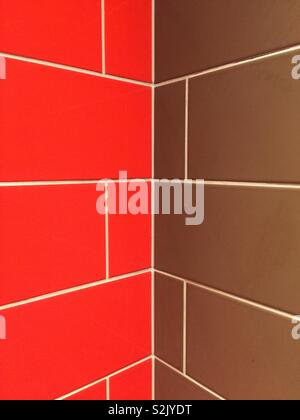 And abstract background of a colourful red and brown tiled wall with diminishing perspective into a corner with copy space - Stock Image