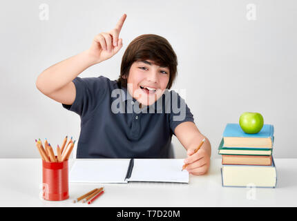 Excited and happy smiling caucasian boy sitting at the desk raising hand with index finger to answer the question in classroom at school - Stock Image