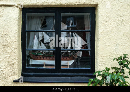 Model sailing ship displayed in a cottage window, Hatherleigh, North Devon, England - Stock Image