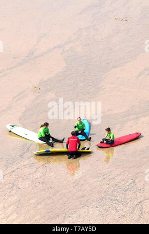 Young holidaymakers listening to their surf instructor during a surfing lesson on Great Western Beach in Newquay in Cornwall. - Stock Image