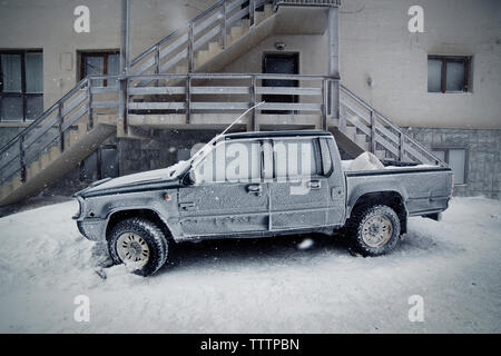 Pick-up truck covered with snow by staircase - Stock Image