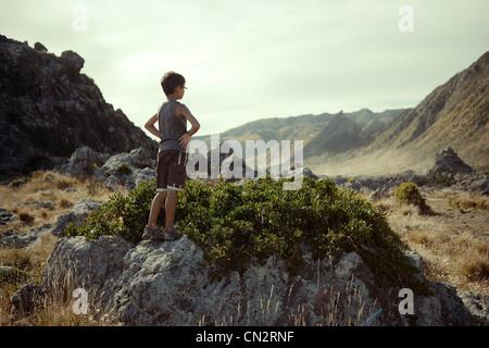 Boy views scenery, Cape Palliser, New Zealand. - Stock Image