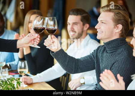 Man tasting with glass of red wine in bistro or restaurant at a celebration - Stock Image