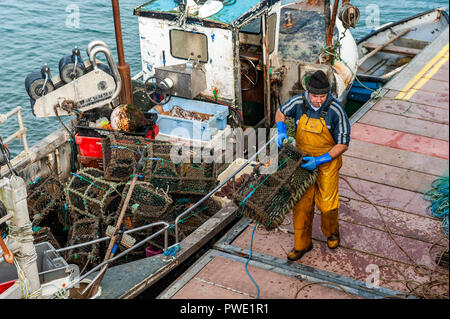 Schull, West Cork, Ireland. 15th Oct, 2018. A local fisherman unloads crab pots off his boat before unloading his catch of crab. The day will remain sunny with unsettled weather forecast for the rest of the week.  Credit: Andy Gibson/Alamy Live News. - Stock Image
