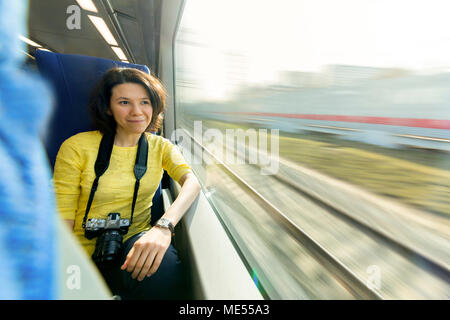 young attractive woman loking in window during her traveling in train - Stock Image