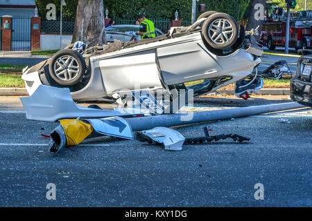 Overturned car with traffice sign down at motor accident. - Stock Image