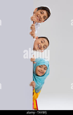young Muslim children peeking out from behind the wall and smiling - Stock Image