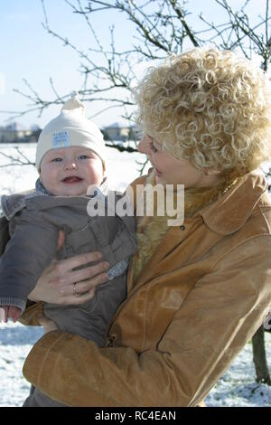 Happy mother and baby boy look at camera in winter outdoors - Stock Image
