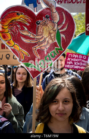 Moscow, Russia. 1st May, 2019 Vegan procession participants hold posters calling for not eating animals in Moscow, Russia - Stock Image