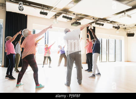 Active seniors dancing, exercising and stretching in circle - Stock Image