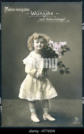 A greeting postcard printed in Switzerland, shows a girl with a bouquet of lilacs. The inscription in German: Happy - Stock Image