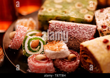 Close up of various turkish delights with nuts and tea glasses - Stock Image