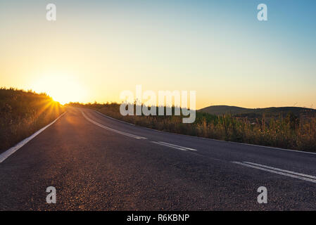 Long road in mountains leading to orange sunset - Stock Image