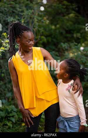 Grandmother and granddaughter pulling shocked faces at each other in a garden - Stock Image