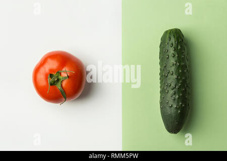 Ripe raw organic tomato cucumber on duotone white light green color combination background. Balanced diet vegan superfoods healthy lifestyle concept.  - Stock Image