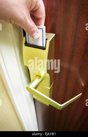 Person's hand inserting a keycard into a hotel room electronic door lock to unlock the door - Stock Image